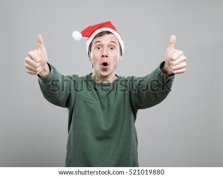 Smiling young man in christmas red hat with thumbs up on grey background