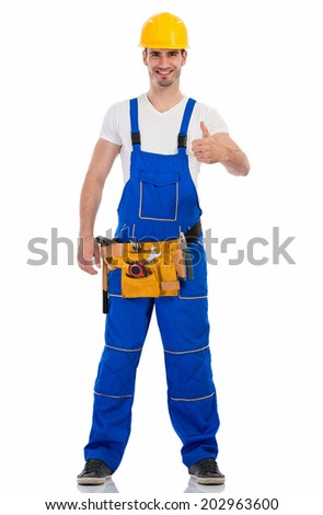 Smiling young man in construction uniform showing thumbs up - stock photo