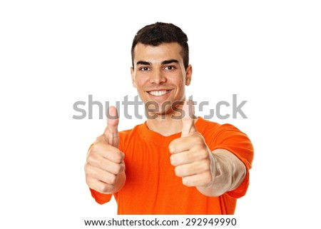 Smiling young man in orange shirt shows you thumbs up - stock photo