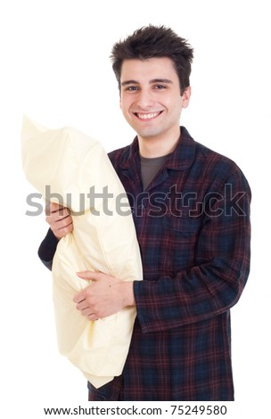 smiling young man in pajamas holding pillow isolated on white background