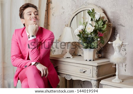 Smiling young man in pink suit sits at table with crossed legs and propping chin with his hand - stock photo