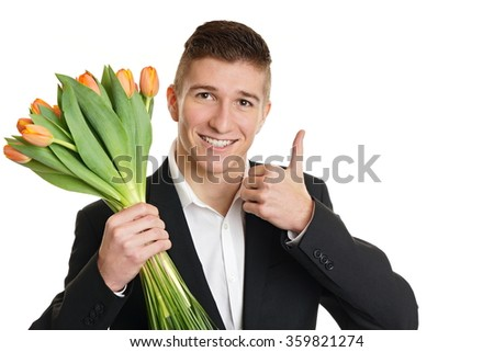 Smiling young man in suit holds beautiful bouquet of tulip and shows you thumb up - stock photo