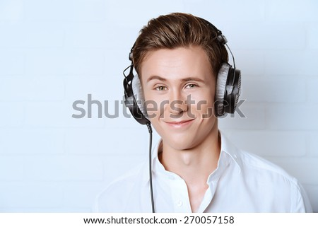 Smiling young man in white shirt listening to music in headphones.  - stock photo