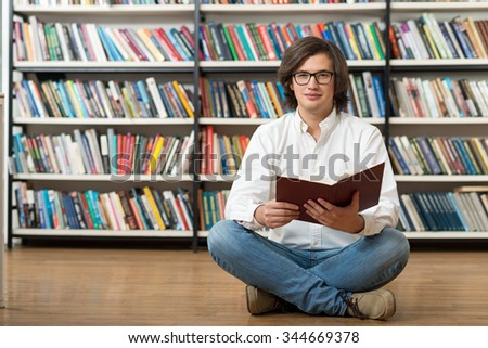 smiling young man in white shirt sitting on the floor with crossed legs in the library with an open book on his knees looking in front of him, book shelves at the background, a concept of reading
