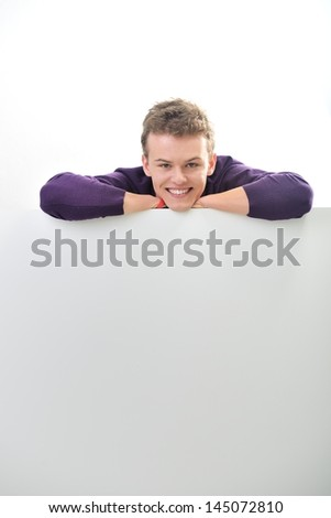 Smiling young man isolated on white leaning on a blank banner