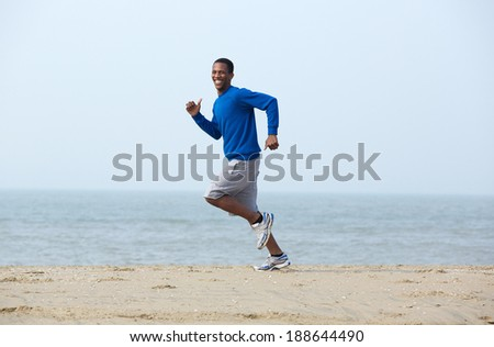 Smiling young man jogging at the beach - stock photo
