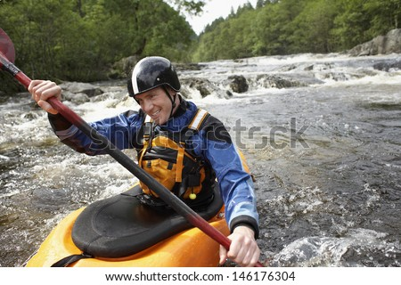 Smiling young man kayaking in the river - stock photo