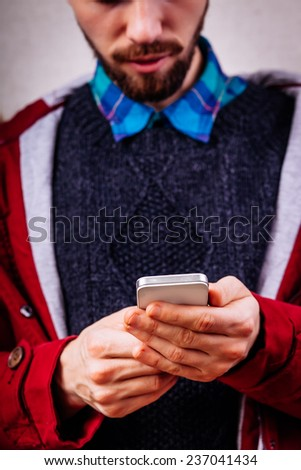 Smiling young man looking at his smart phone while text messaging - stock photo