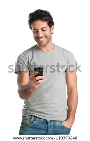 Smiling young man looking at his smart phone while text messaging isolated on white background - stock photo