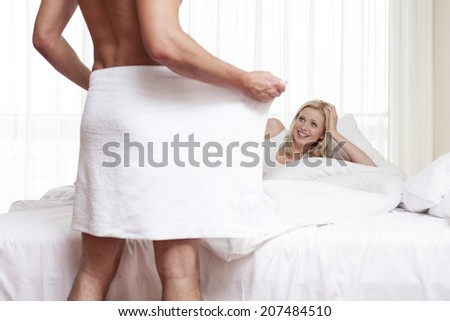 Smiling young man looking at naked man holding towel in bedroom - stock photo