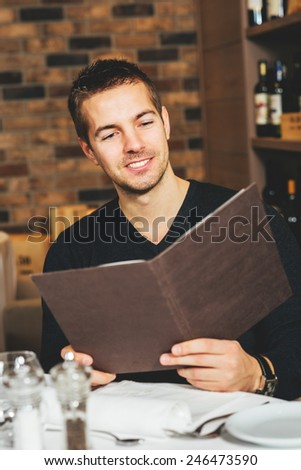 Smiling young man looking at the menu in a restaurant - stock photo