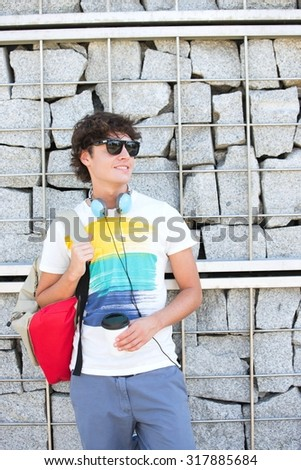 Smiling young man looking away while standing against stone wall - stock photo