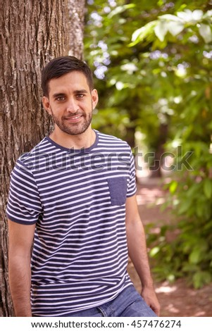 Smiling young man looking happily at the camera in the dappled afternoon sunshine while leaning against a tree wearing casual clothing