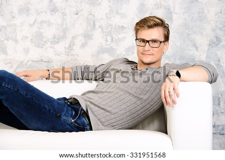 Smiling young man lying relaxed on a sofa.  - stock photo