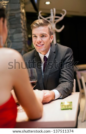 Smiling young man on dating with his girlfriend at the restaurant - stock photo