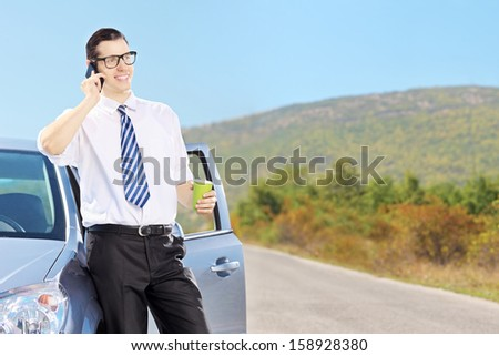 Smiling young man on his automobile talking on a mobile phone and drinking coffee, on an open road - stock photo