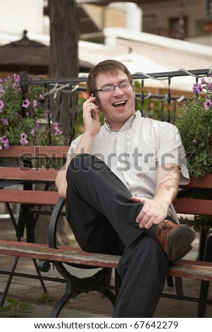 Smiling young man on phone conversation outdoors - stock photo