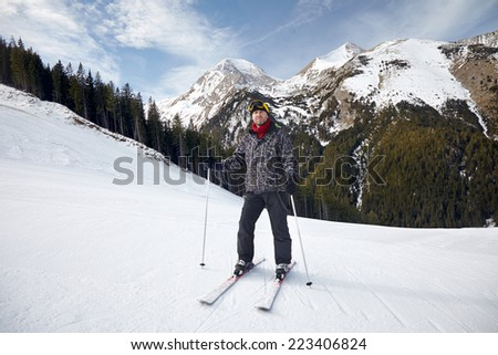 Smiling young man on skis in snow - stock photo