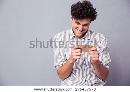 Smiling young man playing on smartphone over gray background - stock photo