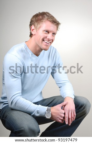 smiling young man posing in squatting pose