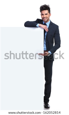 smiling young man presenting a big blank billboard on white background - stock photo