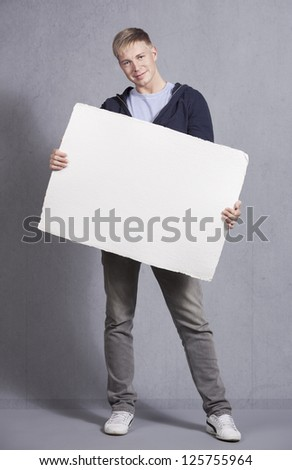 Smiling young man presenting white empty signboard with space for text isolated on grey background. - stock photo