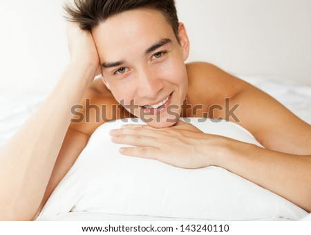 Smiling young man relaxing in the bed - stock photo