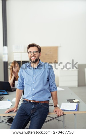 Smiling young man relaxing on the edge of his desk in a large open-plan modern office giving the camera a friendly smile - stock photo