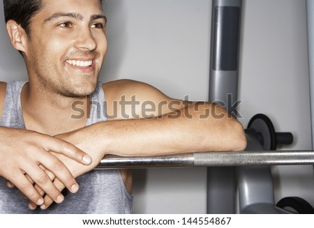Smiling young man resting on barbell after workout at gym