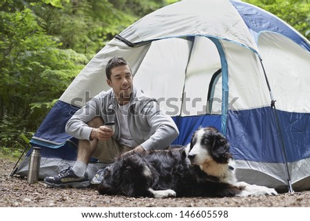 Smiling young man sitting by tent with his pet dog - stock photo