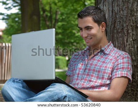 Smiling young man sitting in a forest and using a laptop