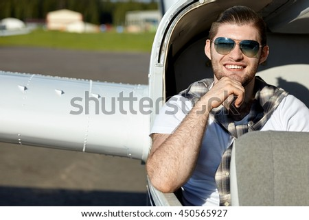 Smiling young man sitting in private air plane to fly on vacation