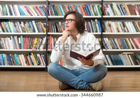 smiling young man sitting on the floor with crossed legs in the library, holding an open book and looking aside touching his chin, book shelves at the background, a concept of thinking.