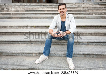 Smiling young man sitting on the stairs - stock photo