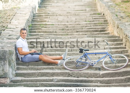 Smiling young man sitting on the stairs and using laptop while his bicycle is beside him - stock photo