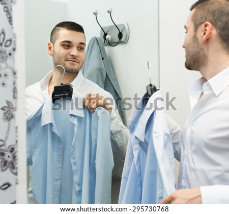Smiling young man standing at boutique changing cubicle - stock photo