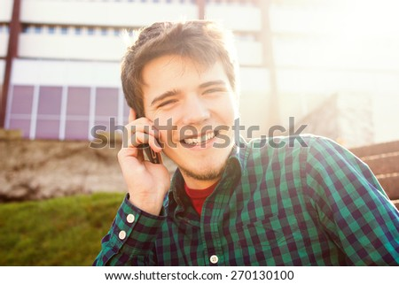 Smiling young man talking on mobile phone in a city .Young smiling student  outdoors talking on cell smart phone.Life style.City - stock photo
