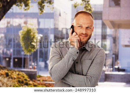 Smiling young man talking on mobilephone outdoors, looking away. - stock photo