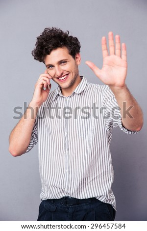 Smiling young man talking on the phone and showing greeting gesture at camera over gray background - stock photo