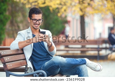 Smiling young man texting on the cellphone - stock photo