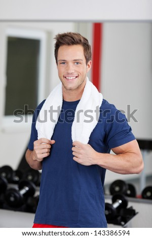 Smiling young man training in the gym with towel around his neck - stock photo