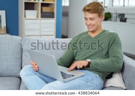 Smiling young man using a laptop computer as he relaxes on a couch surfing the internet - stock photo