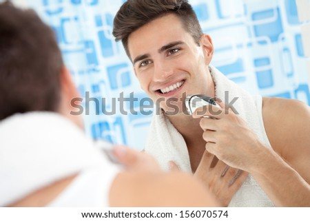 Smiling young man using electric shaver front of mirror - stock photo