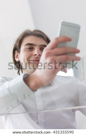 Smiling young man using his phone while standing in his entrepreneurial office space - stock photo