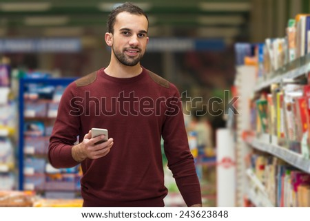 Smiling Young Man Using Mobile Phone While Shopping In Shopping Store - stock photo
