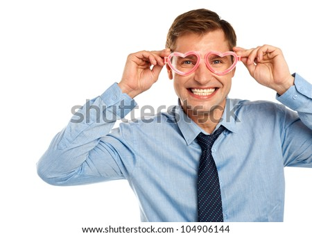 Smiling young man wearing heart shaped eye wear isolated on white - stock photo