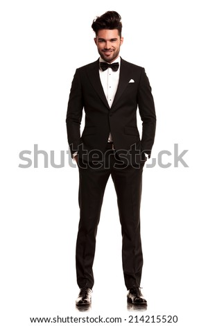 smiling young man wearing tuxedo standing with hands in pockets on white background - stock photo