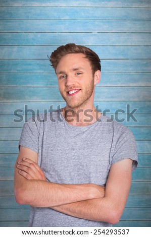 Smiling young man with arms crossed against wooden planks