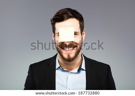smiling young man with blank note on the face, postit