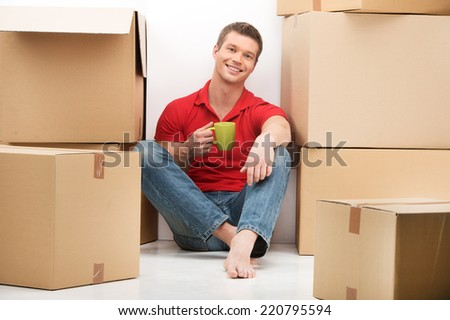 Smiling young man with cardboard box drinking tea. Happy young man moving into new house - stock photo